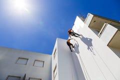 Lavoro industriale dell'alpinista sulla parete bianca Fotografia Stock Libera da Diritti