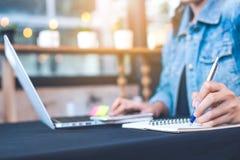 Lavoro manuali della donna in un computer portatile ed in un blocco note di scrittura con la a Fotografia Stock