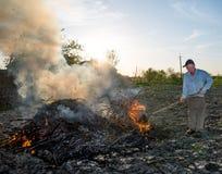 Lavoro nel giardino Rami secchi combustione dell'agricoltore Fotografie Stock