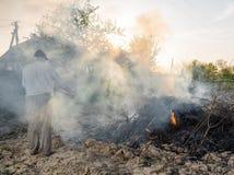 Lavoro nel giardino Rami secchi combustione dell'agricoltore Fotografie Stock Libere da Diritti
