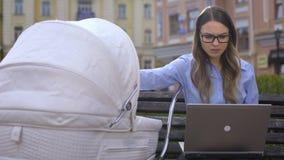 Lavoro occupato di lotta degli impiegati di ufficio sul computer portatile e prendere cura sull'infante in carrozzina stock footage