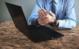 Lavoro sul computer Uomo che soffre dal dolore del polso fotografie stock