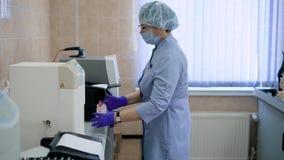 Lavoro in un laboratorio medico Lo specialista è impegnato nell'analisi di sangue L'infermiere o il medico lavora con stock footage