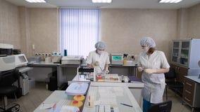 Lavoro in un laboratorio medico Nella struttura, in due infermieri o in medici, sono impegnati nell'analisi dei campioni ottenuti stock footage