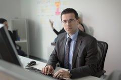 Lavoro votato serio dell'uomo di affari in ufficio sul computer Gente di affari reale dell'economista, non modelli Discussione de