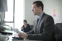 Lavoro votato serio dell'uomo di affari in ufficio sul computer Gente di affari reale dell'economista, non modelli Discussione de Fotografia Stock Libera da Diritti