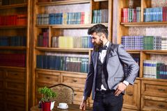 Law, advocacy, professional success, vintage concept. Lawyer stands in vintage interior near table with cup of tea or coffee. Bearded man in elegant suit in royalty free stock images