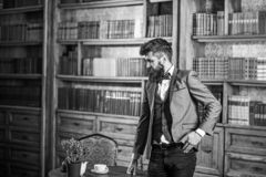 Law, advocacy, professional success, vintage concept. Lawyer stands in vintage interior near table with cup of tea or. Coffee. Bearded man in elegant suit in stock image