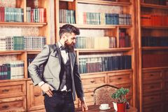 Law, advocacy, professional success, vintage concept. Lawyer stands in vintage interior near table with cup of tea or. Coffee. Bearded man in elegant suit in stock photography