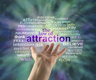 The Law of Attraction Word Cloud. Outstretched female hand with the word ATTRACTION floating above surrounded by a relevant word cloud on a green energy Royalty Free Stock Image