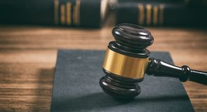 Law or auction gavel on a book, wooden office desk background. Closeup front view royalty free stock images