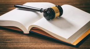 Judge or auction gavel on an open book, wooden desk. Law or auction gavel on an open book, wooden desk, dark background Stock Photo