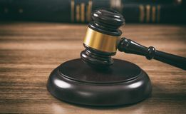 Law or auction gavel on a wooden office desk. Closeup front view stock photo
