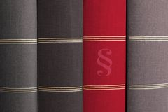 Law book with paragraph symbol, between books. Red law book with paragraph symbol, between grey books - law and order concept royalty free stock images