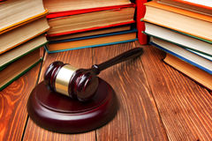 Law book with wooden judges gavel on table in a. Law concept - Law book with a wooden judges gavel on table in a courtroom or law enforcement office stock images