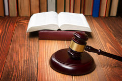 Law book with wooden judges gavel on table in a courtroom or law enforcement office. Stock Images