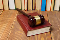Law book with wooden judges gavel on table in a courtroom or law enforcement office. Stock Photos