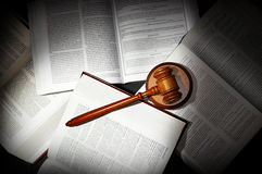Law books and gavel. Assorted open law books with legal gavel, in dramatic light Stock Photo