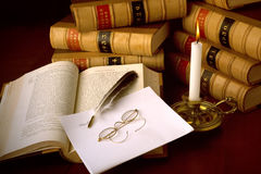 Law books and Quill. Old case reports, candle, quill pen and glasses Stock Images