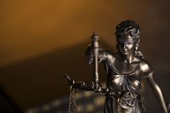 Law theme. Blind justice symbol - Themis. Law code. Statue of justice and  books. Brown background. Place for text Stock Image