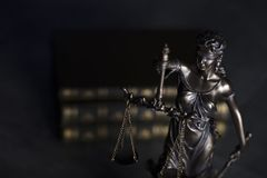 Law theme. Blind justice symbol - Themis. Law code. Statue of justice and  books. Dark  background. Place for text Royalty Free Stock Photo