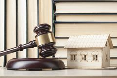 Law concept -Miniature house, books with wooden judges gavel on table in a courtroom or enforcement office.