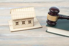 Law concept . Model house with wooden judge gavel on table in a courtroom or enforcement office.