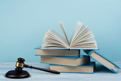Law concept open book with wooden judges gavel on table in a courtroom or law enforcement office, blue background. Copy Stock Photo