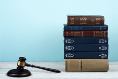 Law concept open book with wooden judges gavel on table in a courtroom or law enforcement office, blue background. Copy Royalty Free Stock Image