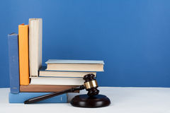 Law concept open book with wooden judges gavel on table in a courtroom or law enforcement office, blue background. Copy. Space for text stock photos
