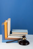 Law concept open book with wooden judges gavel on table in a courtroom or law enforcement office, blue background. Copy space for Stock Photo