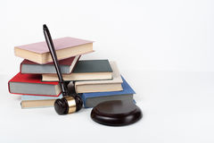 Law concept open book with wooden judges gavel on table in a courtroom or law enforcement office, white background. Copy Stock Images