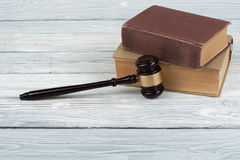 Law concept - Open law book with a wooden judges gavel on table in a courtroom or law enforcement office  on Stock Photo