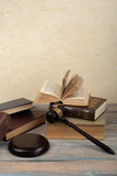 Law concept - Open law book with a wooden judges gavel on table in a courtroom or law enforcement office  on Royalty Free Stock Photography