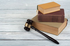 Law concept - Open law book with a wooden judges gavel on table in a courtroom or law enforcement office isolated on Stock Image