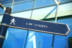 Law courts direction sign. With office block windows in the background Royalty Free Stock Image