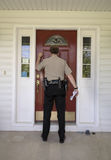 Law enforcement officer knocking on a door Stock Images
