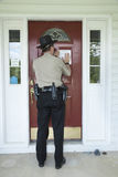 Law enforcement officer posting an eviction notice. Royalty Free Stock Photo