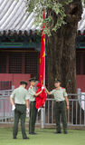 Law enforcement officers raising the Chinese flag Royalty Free Stock Image