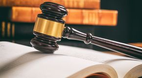 Judge gavel on an open book, wooden desk, law books background Stock Photography