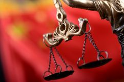 Scales of Justice, Justitia, Lady Justice in front of the flag of China. Stock Photo