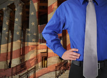 Law Justice Man with Flag. A law man is standing against a government building and American flag in the background. Add your message to the copyspace Royalty Free Stock Photo
