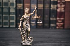 Scales of Justice, Lady Justice and Law books in the background. royalty free stock images