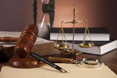 Law and justice stuff on wooden table, dark background Royalty Free Stock Photos