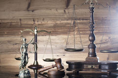 Law and justice theme. Gavel of judge, scales of justice and Themis  on wooden background Royalty Free Stock Photos