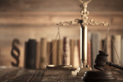 Law and justice theme. Mallet of judge. Scale of justice. Legal code. Wooden table. Stone background Stock Image
