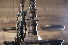 Law and justice theme. Scales of justice and Themis   on wooden background Royalty Free Stock Photography