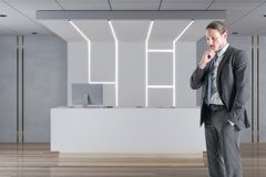 Law and legal concept. Thoughtful young businessman standing in modern interior with reception desk. Law and legal concept royalty free stock photography