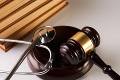 Law mallet or Judge gavel and medical stethoscope. Near law textbook in library archive study room, close-up. Forensic medicine investigation or malpractice Royalty Free Stock Image