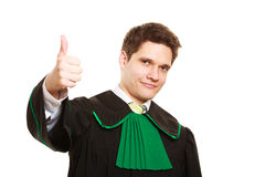 Law. Man lawyer in polish gown showing thumb up Royalty Free Stock Image